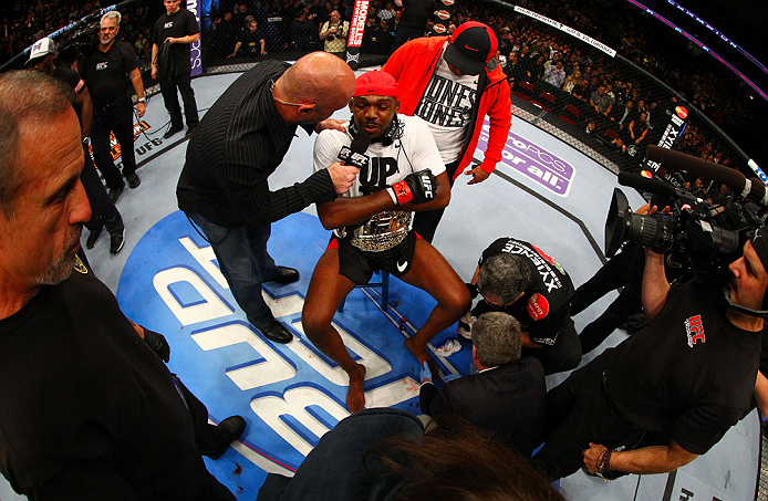 NEWARK, NJ - APRIL 27:  Jon Jones (C) has his broken toe tended to while he is interviewed by Joe Rogan (R) after winning by knockout in round one against Chael Sonnen in their light heavyweight championship bout during the UFC 159 event at the Prudential Center on April 27, 2013 in Newark, New Jersey.  (Photo by Al Bello/Zuffa LLC/Zuffa LLC Via Getty Images)