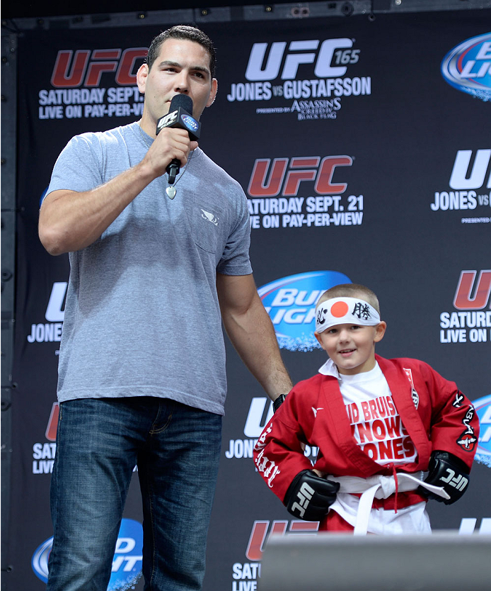 TORONTO, CANADA - SEPTEMBER 20:  UFC Middleweight Champion Chris Weidman interacts with a young fan on stage during a Q&A session before the UFC 165 weigh-in at the Maple Leaf Square on September 20, 2013 in Toronto, Ontario, Canada. (Photo by Jeff Bottari/Zuffa LLC/Zuffa LLC via Getty Images)