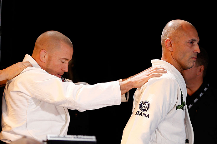 LAS VEGAS, NV - NOVEMBER 13: UFC legend Royce Gracie (R) leads UFC welterweight champion Georges St-Pierre (L) onto the stage before an open workout session for media inside the Hollywood Theatre at the MGM Grand Hotel/Casino on November 13, 2013 in Las Vegas, Nevada. (Photo by Josh Hedges/Zuffa LLC/Zuffa LLC via Getty Images)