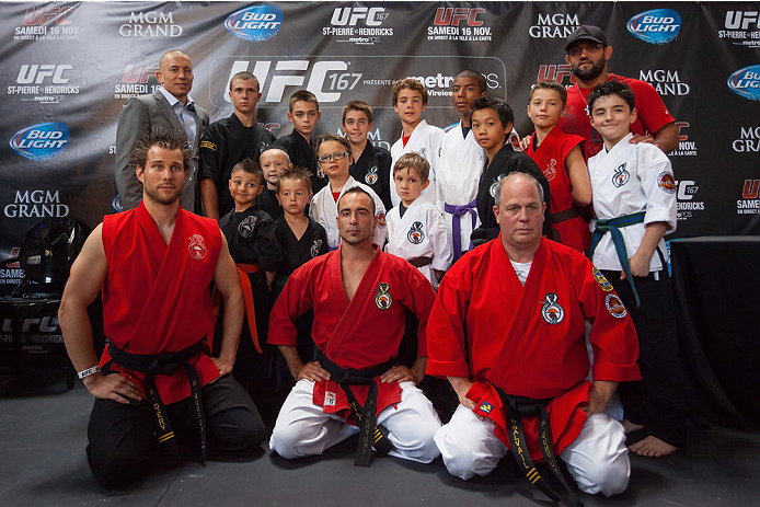 MONTREAL, CANADA - AUGUST 1: Georges St Pierre and Johny Hendricks take a moment with kids and instructors from the Sunfouki karate school of Montreal during the Georges St Pierre and Johny Hendricks Press Tour on August 1, 2013 in Montreal, Quebec, Canada. (Francois Laplante/Zuffa LLC via Getty Images)