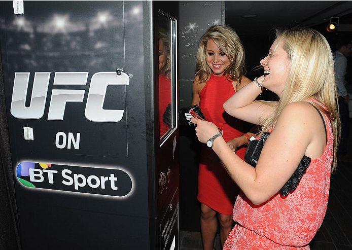 LONDON, ENGLAND - AUGUST 03:  Carly Baker (L) and her friend giggle at their photographs taken in the photobooth at the Paramount Club during the Jon Jones and Alex Gustafsson Press Tour of London on August 3, 2013 in London, England.  (Photo by Christopher Lee/Zuffa LLC/Zuffa LLC via Getty Images)