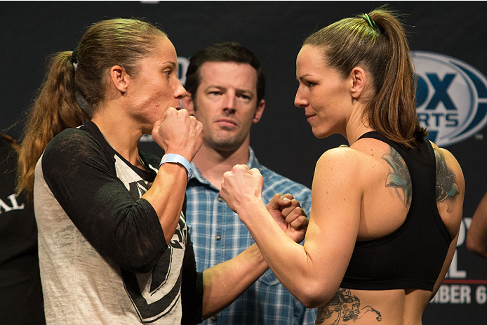 CLARKSVILLE, TN - NOVEMBER 5:  Liz Carmouche (L) and Alexis Davis (R) face off during the UFC Fight For the Troops weigh-in at the Fort Campbell Sabre Air Field hanger on November 5, 2013 in Clarksville, Tennessee. (Photo by Ed Mulholland/Zuffa LLC/Zuffa LLC via Getty Images)