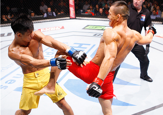 MACAU - AUGUST 23:  Ning Guangyou throws a knee at Yang Jianping in their featherweight fight during the UFC Fight Night event at the Venetian Macau on August 23, 2014 in Macau. (Photo by Mitch Viquez/Zuffa LLC/Zuffa LLC via Getty Images)