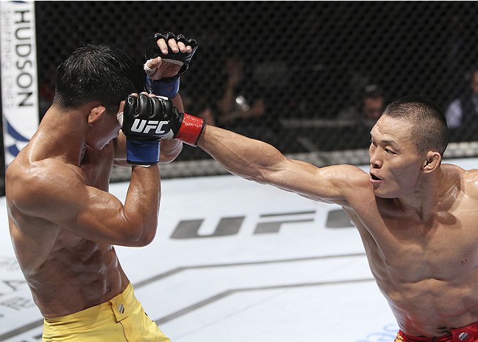 MACAU - AUGUST 23:  Ning Guangyou punches Yang Jianping in their featherweight fight during the UFC Fight Night event at the Venetian Macau on August 23, 2014 in Macau. (Photo by Mitch Viquez/Zuffa LLC/Zuffa LLC via Getty Images)