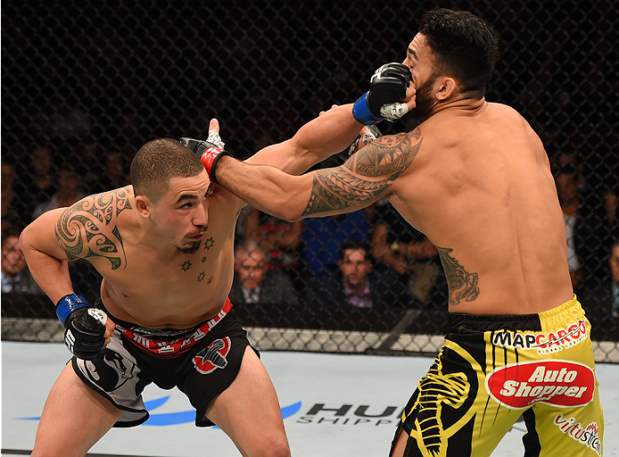 ADELAIDE, AUSTRALIA - MAY 10:   (L-R) Robert Whittaker punches Brad Tavares in their middleweight bout during the UFC Fight Night event at the Adelaide Entertainment Centre on May 10, 2015 in Adelaide, Australia. (Photo by Josh Hedges/Zuffa LLC/Zuffa LLC via Getty Images)