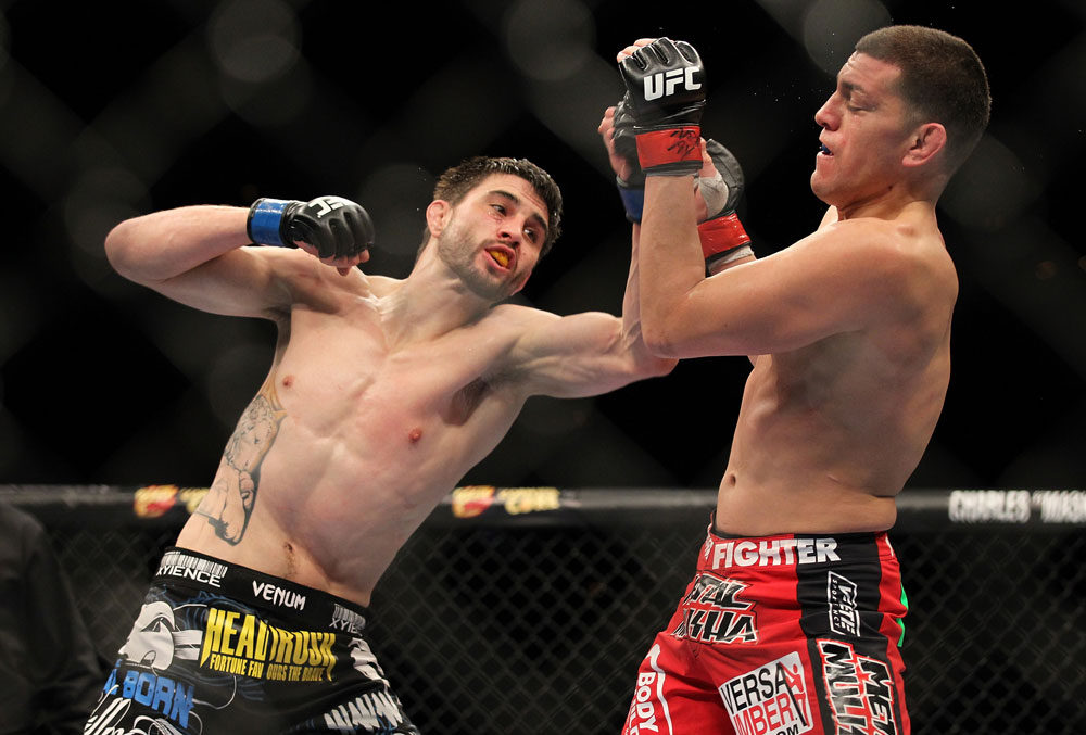 LAS VEGAS - FEBRUARY 04:  Carlos Condit (left) punches Nick Diaz during the UFC 143 event at Mandalay Bay Events Center on February 4, 2012 in Las Vegas, Nevada.  (Photo by Josh Hedges/Zuffa LLC/Zuffa LLC via Getty Images) *** Local Caption *** Carlos Condit; Nick Diaz