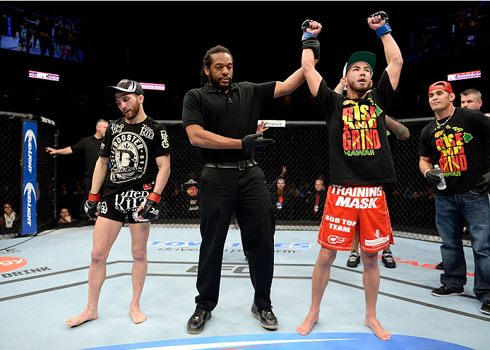DULUTH, GA - JANUARY 15: (R-L) Louis Smolka reacts after winning by decision against Alpetkin Ozkilic in their featherweight fight during the UFC Fight Night event inside The Arena at Gwinnett Center on January 15, 2014 in Duluth, Georgia. (Photo by Jeff Bottari/Zuffa LLC/Zuffa LLC via Getty Images)