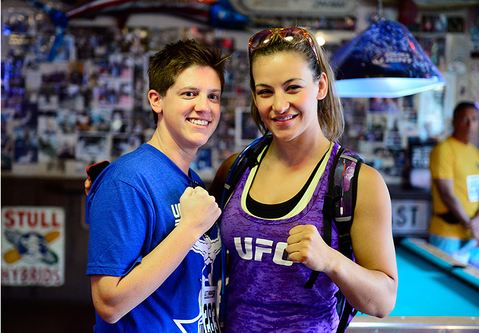 LAS VEGAS, NV - JULY 4:  Miesha Tate takes a picture with a fan before the first annual Ulti-man 5K run during UFC International Fight Week at Hogs and Heifers on July 4, 2014 in Las Vegas, Nevada. Proceeds will help support Three Square Food Bank. (Photo by Brandon Magnus/Zuffa LLC/Zuffa LLC via Getty Images)