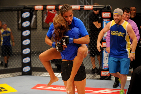 LAS VEGAS, NV - JUNE 6:  Coach Miesha Tate celebrates with Julianna Pena (blue shorts) after she submits Shayna Baszler (not pictured) in their preliminary fight during filming of season eighteen of The Ultimate Fighter on June 6, 2013 in Las Vegas, Nevada. (Photo by Al Powers/Zuffa LLC/Zuffa LLC via Getty Images)