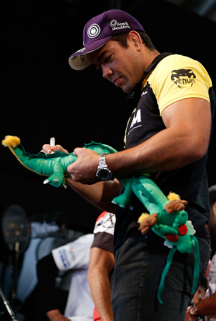 "RIO DE JANEIRO, BRAZIL - AUGUST 01:  Lyoto ""The Dragon"" Machida signs a stuffed dragon doll for a fan after a pre-fight press conference at Circo Voador on August 1, 2013 in Rio de Janeiro, Brazil. (Photo by Josh Hedges/Zuffa LLC/Zuffa LLC via Getty Images)"