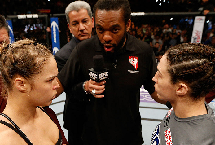 LAS VEGAS, NV - FEBRUARY 22:  Ronda Rousey (left) and Sara McMann (right) listen to instructions from referee Herb Dean (center) before their women's bantamweight championship bout during UFC 170 inside the Mandalay Bay Events Center on February 22, 2014 in Las Vegas, Nevada. (Photo by Josh Hedges/Zuffa LLC/Zuffa LLC via Getty Images) *** Local Caption *** Ronda Rousey; Sara McMann; Herb Dean