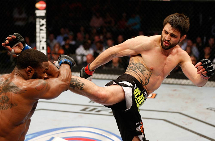 DALLAS, TX - MARCH 15:  (R-L) Carlos Condit kicks Tyron Woodley in their welterweight bout at UFC 171 inside American Airlines Center on March 15, 2014 in Dallas, Texas. (Photo by Josh Hedges/Zuffa LLC/Zuffa LLC via Getty Images)