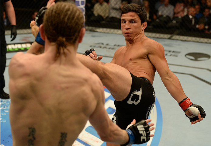 BALTIMORE, MD - APRIL 26:  (R-L) Joseph Benavidez kicks Timothy Elliott in their bantamweight bout during the UFC 172 event at the Baltimore Arena on April 26, 2014 in Baltimore, Maryland. (Photo by Patrick Smith/Zuffa LLC/Zuffa LLC via Getty Images)