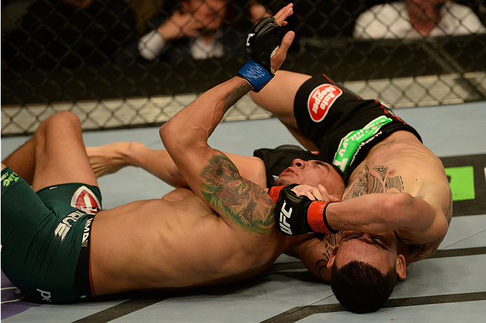 BALTIMORE, MD - APRIL 26:  (R-L) Max Holloway secures a guillotine choke against Andre Fili in their featherweight bout during the UFC 172 event at the Baltimore Arena on April 26, 2014 in Baltimore, Maryland. (Photo by Patrick Smith/Zuffa LLC/Zuffa LLC via Getty Images)