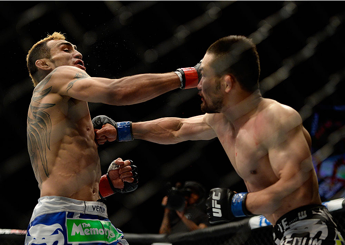 LAS VEGAS, NV - MAY 24:  (R-L) Katsunori Kikuno punches Tony Ferguson in their lightweight bout during the UFC 173 event at the MGM Grand Garden Arena on May 24, 2014 in Las Vegas, Nevada. (Photo by Jeff Bottari/Zuffa LLC/Zuffa LLC via Getty Images)