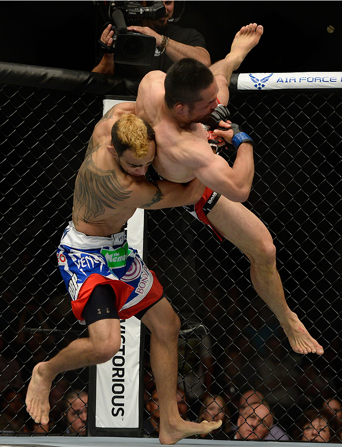 LAS VEGAS, NV - MAY 24:  (L-R) Tony Ferguson takes down Katsunori Kikuno in their lightweight bout during the UFC 173 event at the MGM Grand Garden Arena on May 24, 2014 in Las Vegas, Nevada. (Photo by Jeff Bottari/Zuffa LLC/Zuffa LLC via Getty Images)