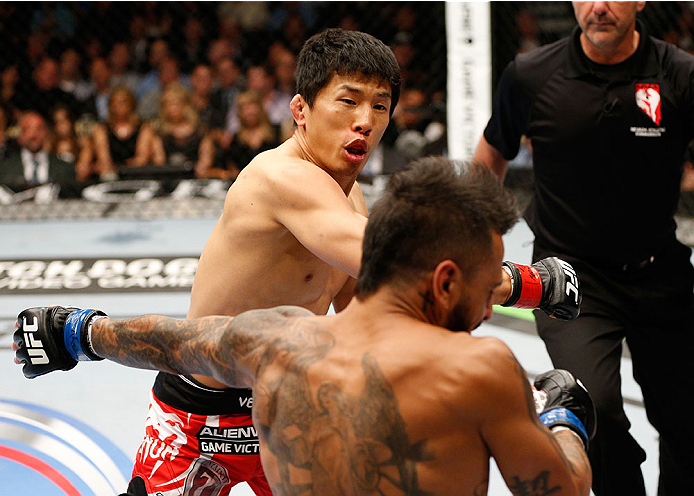 LAS VEGAS, NV - MAY 24:  (L-R) Takeya Mizugaki punches Francisco Rivera in their bantamweight bout during the UFC 173 event at the MGM Grand Garden Arena on May 24, 2014 in Las Vegas, Nevada. (Photo by Josh Hedges/Zuffa LLC/Zuffa LLC via Getty Images)