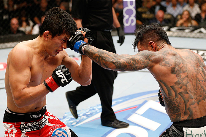 LAS VEGAS, NV - MAY 24:  (R-L) Francisco Rivera punches Takeya Mizugaki in their bantamweight bout during the UFC 173 event at the MGM Grand Garden Arena on May 24, 2014 in Las Vegas, Nevada. (Photo by Josh Hedges/Zuffa LLC/Zuffa LLC via Getty Images)