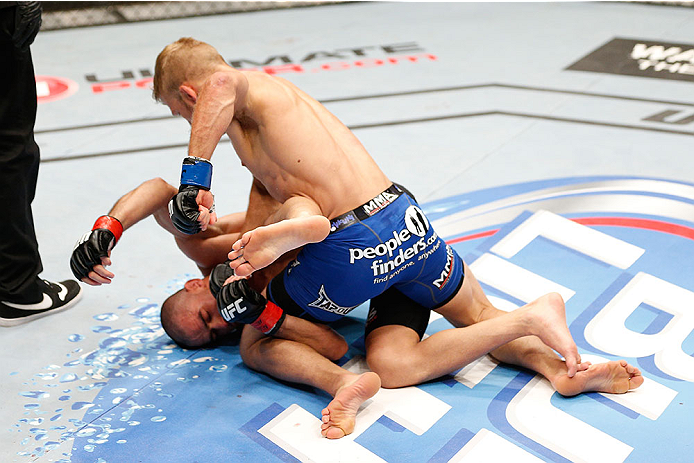 LAS VEGAS, NV - MAY 24:  T.J. Dillashaw (top) punches Renan Barao in their bantamweight championship bout during the UFC 173 event at the MGM Grand Garden Arena on May 24, 2014 in Las Vegas, Nevada. (Photo by Josh Hedges/Zuffa LLC/Zuffa LLC via Getty Images)