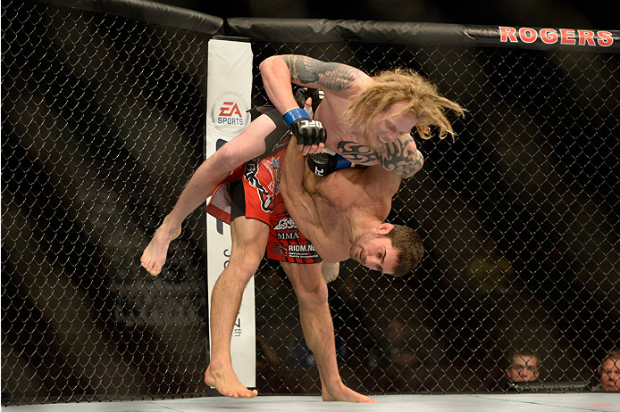 VANCOUVER, BC - JUNE 14:  (R-L) Jason Saggo takes down Josh Shockley during the UFC 174 event at Rogers Arena on June 14, 2014 in Vancouver, British Columbia, Canada. (Photo by Jeff Bottari/Zuffa LLC/Zuffa LLC via Getty Images)