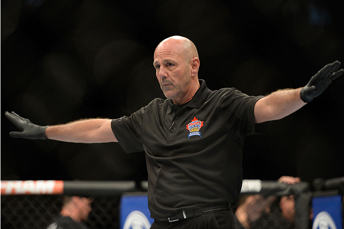 VANCOUVER, BC - JUNE 14:  Referee Yves Lavigne calls the Michinori Tanaka and Roland Delorme fight during the UFC 174 event at Rogers Arena on June 14, 2014 in Vancouver, British Columbia, Canada. (Photo by Jeff Bottari/Zuffa LLC/Zuffa LLC via Getty Images)