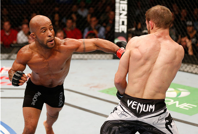 "VANCOUVER, BC - JUNE 14:  (L-R) Demetrious ""Mighty Mouse"" Johnson delivers a punch against Ali Bagautinov in their UFC flyweight championship bout at Rogers Arena on June 14, 2014 in Vancouver, Canada.  (Photo by Josh Hedges/Zuffa LLC/Zuffa LLC via Getty Images)"