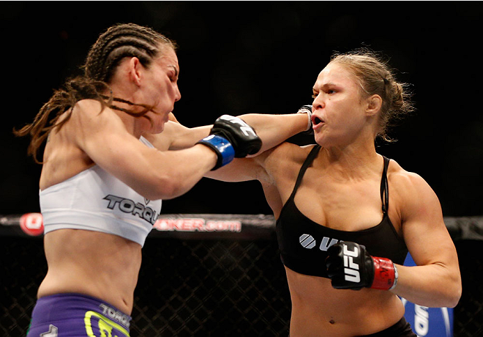LAS VEGAS, NV - JULY 05:  (R-L) UFC women's bantamweight champion Ronda Rousey punches Alexis Davis in their UFC women's bantamweight championship fight at UFC 175 inside the Mandalay Bay Events Center on July 5, 2014 in Las Vegas, Nevada.  (Photo by Josh Hedges/Zuffa LLC/Zuffa LLC via Getty Images)