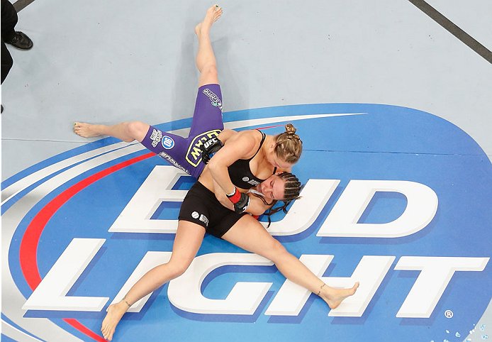 LAS VEGAS, NV - JULY 05:  UFC women's bantamweight champion Ronda Rousey (top) punches Alexis Davis while controlling her body in their UFC women's bantamweight championship fight at UFC 175 inside the Mandalay Bay Events Center on July 5, 2014 in Las Vegas, Nevada.  (Photo by Josh Hedges/Zuffa LLC/Zuffa LLC via Getty Images)