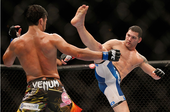 LAS VEGAS, NV - JULY 05:  (R-L) UFC middleweight champion Chris Weidman kicks Lyoto Machida in their UFC middleweight championship fight at UFC 175 inside the Mandalay Bay Events Center on July 5, 2014 in Las Vegas, Nevada.  (Photo by Josh Hedges/Zuffa LLC/Zuffa LLC via Getty Images)