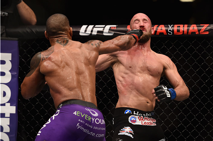 LAS VEGAS, NV - JANUARY 03:  (L) Hector Lombard punches Josh Burkman in their welterweight bout during the UFC 182 event on at the MGM Grand Garden Arena January 3, 2015 in Las Vegas, Nevada.  (Photo by Jeff Bottari/Zuffa LLC/Zuffa LLC via Getty Images)