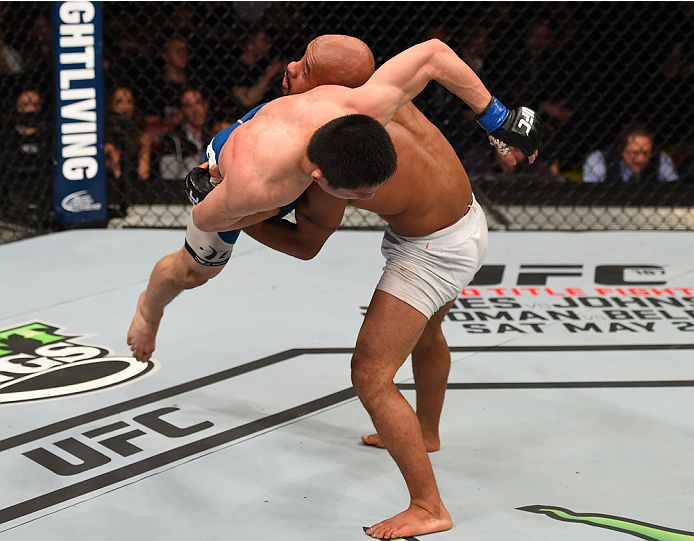 MONTREAL, QC - APRIL 25:   (R-L) Demetrious Johnson of the United States takes down Kyoji Horiguchi of Japan in their UFC flyweight championship bout during the UFC 186 event at the Bell Centre on April 25, 2015 in Montreal, Quebec, Canada. (Photo by Josh Hedges/Zuffa LLC/Zuffa LLC via Getty Images)