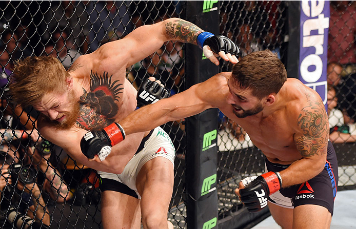 Chad Mendes punches Conor McGregor in their UFC interim featherweight title fight during the UFC 189 event inside MGM Grand Garden Arena on July 11, 2015 in Las Vegas, Nevada. (Photo by Josh Hedges/Zuffa LLC)