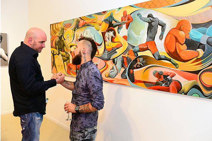 LAS VEGAS, NV - JULY 1:  (R-L) Artist Brian Kirhagis showcases his artwork to UFC President Dana White at the Art of Fighting Exhibition to kick off the UFC International Fight Week at The Gallery on 1217 on July 1, 2014 in Las Vegas, Nevada. (Photo by Jeff Bottari/Zuffa LLC/Zuffa LLC via Getty Images)