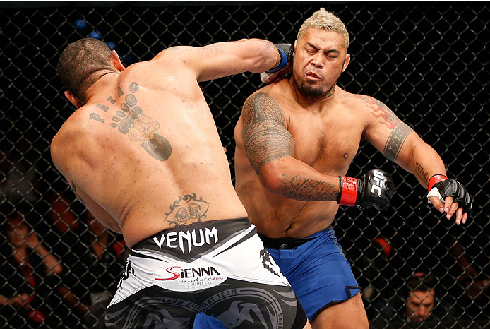 "BRISBANE, AUSTRALIA - DECEMBER 07:  (L-R) Antonio ""Bigfoot"" Silva knocks down Mark Hunt with a punch in the first round of their heavyweight fight during the UFC Fight Night event at the Brisbane Entertainment Centre on December 7, 2013 in Brisbane, Australia. (Photo by Josh Hedges/Zuffa LLC/Zuffa LLC via Getty Images)"