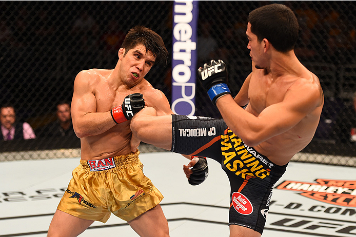 PHOENIX, AZ - DECEMBER 13:  (R-L) Dustin Kimura kicks the body of Henry Cejudo in their bantamweight fight during the UFC Fight Night event at the U.S. Airways Center on December 13, 2014 in Phoenix, Arizona.  (Photo by Josh Hedges/Zuffa LLC/Zuffa LLC via Getty Images)