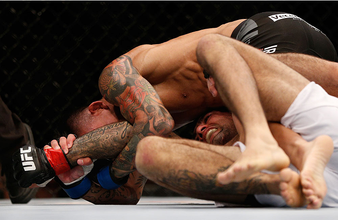 SINGAPORE - JANUARY 04:  Russell Doane (top) attempts to secure an arm lock submission against Leandro Issa in their bantamweight bout during the UFC Fight Night event at the Marina Bay Sands Resort on January 4, 2014 in Singapore. (Photo by Josh Hedges/Zuffa LLC/Zuffa LLC via Getty Images)