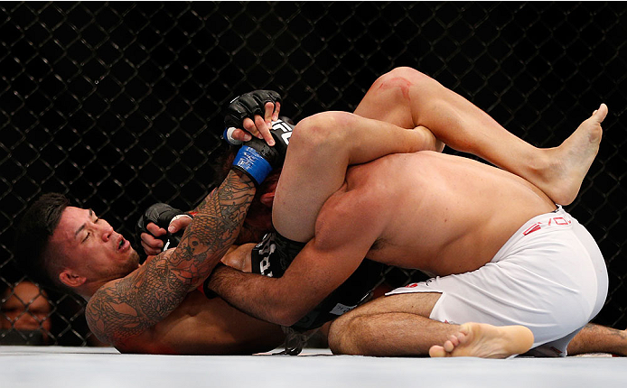 SINGAPORE - JANUARY 04:  (L-R) Russell Doane secures a triangle choke submission against Leandro Issa in their bantamweight bout during the UFC Fight Night event at the Marina Bay Sands Resort on January 4, 2014 in Singapore. (Photo by Josh Hedges/Zuffa LLC/Zuffa LLC via Getty Images)