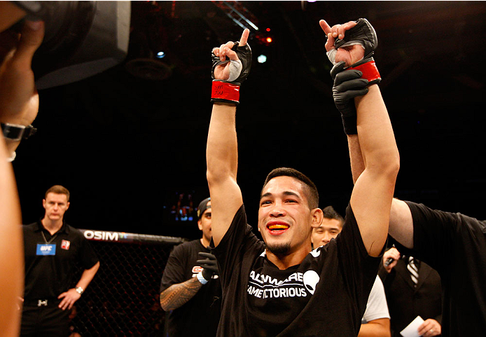 SINGAPORE - JANUARY 04:  Dustin Kimura celebrates his win over Jon Delos Reyes in their bantamweight bout during the UFC Fight Night event at the Marina Bay Sands Resort on January 4, 2014 in Singapore. (Photo by Mitch Viquez/Zuffa LLC/Zuffa LLC via Getty Images)