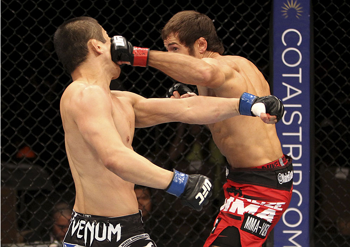 SINGAPORE - JANUARY 04:  Mairbek Taisumov lands a bunch on Bang Tae Hyun in their lightweight bout during the UFC Fight Night event at the Marina Bay Sands Resort on January 4, 2014 in Singapore. (Photo by Mitch Viquez/Zuffa LLC/Zuffa LLC via Getty Images)