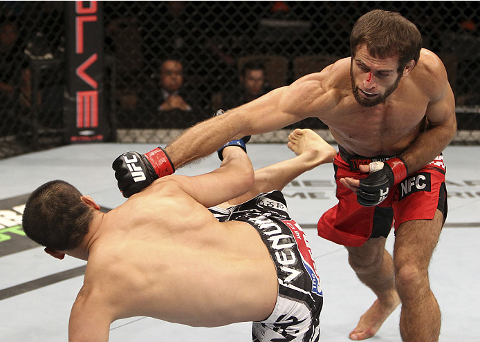 SINGAPORE - JANUARY 04:  Mairbek Taisumov goes for a punch on Bang Tae Hyun in their lightweight bout during the UFC Fight Night event at the Marina Bay Sands Resort on January 4, 2014 in Singapore. (Photo by Mitch Viquez/Zuffa LLC/Zuffa LLC via Getty Images)