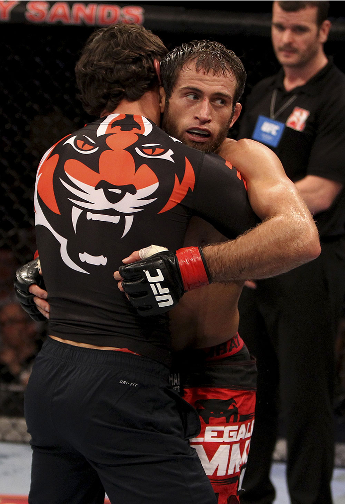 SINGAPORE - JANUARY 04:  Mairbek Taisumov is given a hug after his win  over Bang Tae Hyun in their lightweight bout during the UFC Fight Night event at the Marina Bay Sands Resort on January 4, 2014 in Singapore. (Photo by Mitch Viquez/Zuffa LLC/Zuffa LLC via Getty Images)