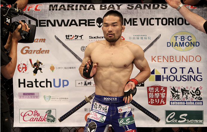 SINGAPORE - JANUARY 04:  Katsunori Kikuno stands in front of his banner before his lightweight bout with Quinn Mulhern during the UFC Fight Night event at the Marina Bay Sands Resort on January 4, 2014 in Singapore. (Photo by Mitch Viquez/Zuffa LLC/Zuffa LLC via Getty Images)