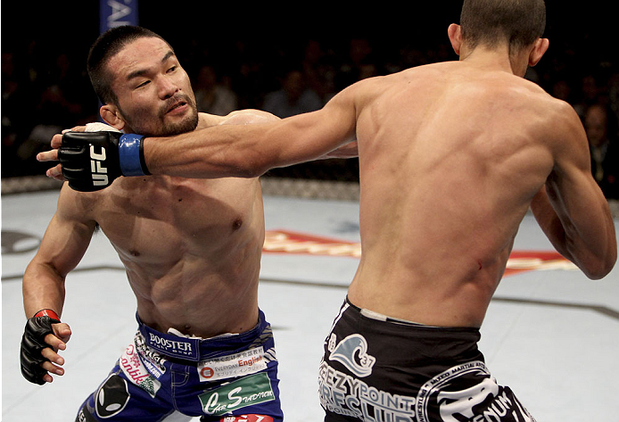 SINGAPORE - JANUARY 04:  Katsunori Kikuno goes for a punch on Quinn Mulhern in their lightweight bout during the UFC Fight Night event at the Marina Bay Sands Resort on January 4, 2014 in Singapore. (Photo by Mitch Viquez/Zuffa LLC/Zuffa LLC via Getty Images)