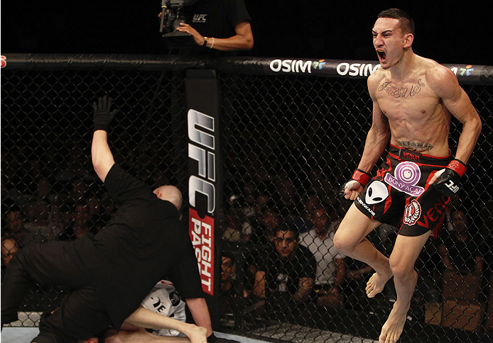 SINGAPORE - JANUARY 04:  Max Holloway celebrates his win over Will Chope in their featherweight bout during the UFC Fight Night event at the Marina Bay Sands Resort on January 4, 2014 in Singapore. (Photo by Mitch Viquez/Zuffa LLC/Zuffa LLC via Getty Images)