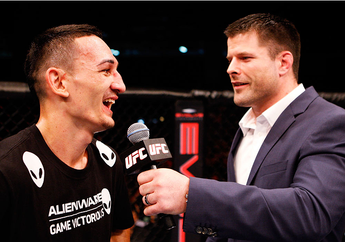 SINGAPORE - JANUARY 04:  (L-R) Max Holloway has a laugh with Brian Stann after his win over Will Chope in their featherweight bout during the UFC Fight Night event at the Marina Bay Sands Resort on January 4, 2014 in Singapore. (Photo by Mitch Viquez/Zuffa LLC/Zuffa LLC via Getty Images)