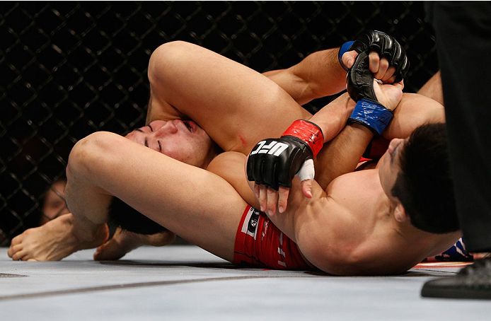 SINGAPORE - JANUARY 04:  (R-L) Kang Kyung Ho attempts an arm bar submission against Shunichi Shimizu in their bantamweight bout during the UFC Fight Night event at the Marina Bay Sands Resort on January 4, 2014 in Singapore. (Photo by Josh Hedges/Zuffa LLC/Zuffa LLC via Getty Images)