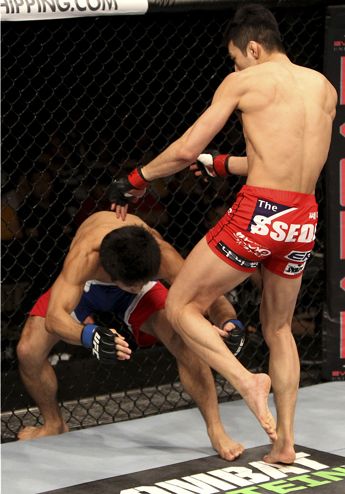 SINGAPORE - JANUARY 04:  Kang Kyung Ho goes for a knee on Shunichi Shimizu in their bantamweight bout during the UFC Fight Night event at the Marina Bay Sands Resort on January 4, 2014 in Singapore. (Photo by Mitch Viquez/Zuffa LLC/Zuffa LLC via Getty Images)