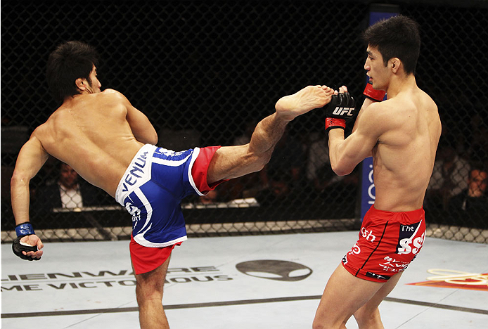 SINGAPORE - JANUARY 04: Shunichi Shimizu goes for a spinning back kick onKang Kyung Ho in their bantamweight bout during the UFC Fight Night event at the Marina Bay Sands Resort on January 4, 2014 in Singapore. (Photo by Mitch Viquez/Zuffa LLC/Zuffa LLC via Getty Images)