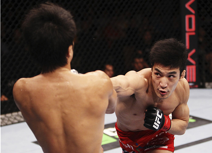 SINGAPORE - JANUARY 04: Kang Kyung Ho goes for a punch on Shunichi Shimizu in their bantamweight bout during the UFC Fight Night event at the Marina Bay Sands Resort on January 4, 2014 in Singapore. (Photo by Mitch Viquez/Zuffa LLC/Zuffa LLC via Getty Images)