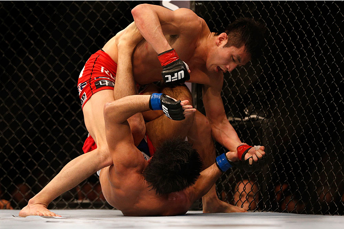 SINGAPORE - JANUARY 04:  (L-R) Kang Kyung Ho punches Shunichi Shimizu in their bantamweight bout during the UFC Fight Night event at the Marina Bay Sands Resort on January 4, 2014 in Singapore. (Photo by Josh Hedges/Zuffa LLC/Zuffa LLC via Getty Images)